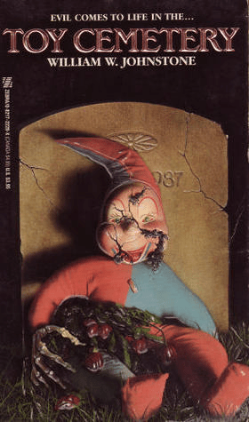 Cover of Toy Cemetery by William W Johnstone. Cover shows a doll with a cracked face, dressed as a jester. The doll is resting against a headstone in a cemetery. The doll has the hands of a skeleton and dirt is spilling from its cracked face.