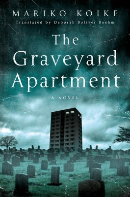 Cover of The Graveyard Apartment by Mariko Koike. Cover shows a lone apartment building surrounded by graves. Cover is in shades of grey and deep blue green.