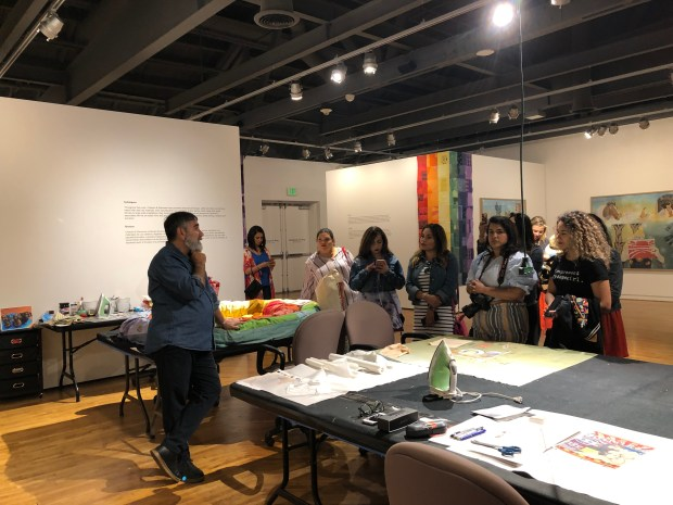 Artist, Leo Chiachio, talking with several women at his art table which is piled with various fabrics and images for his next project