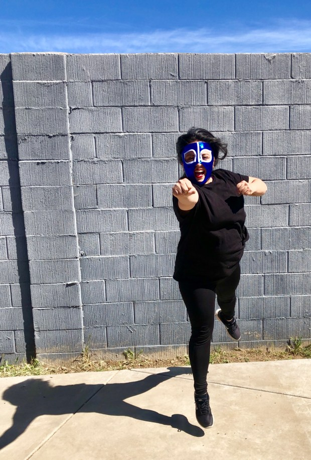 Woman dressed in black leaps forward with fists out front. She is wearing a shiny blue luchador mask.