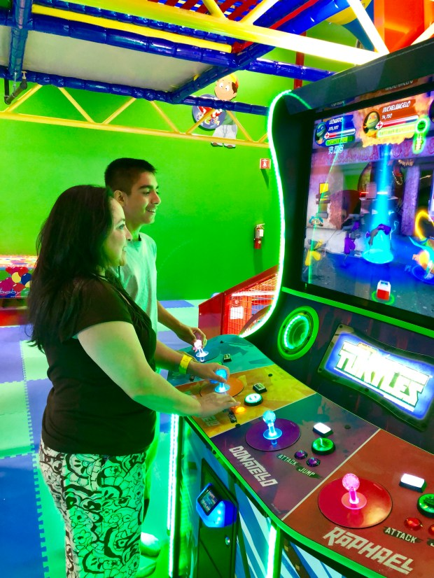 Mother and son standing in front of an arcade game
