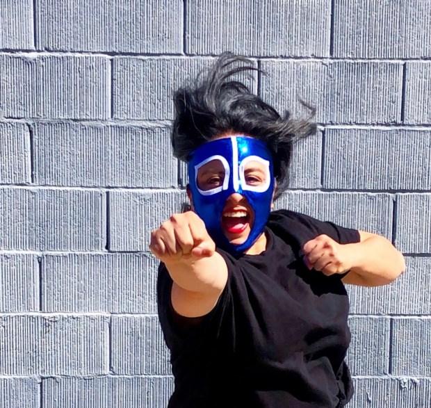 woman shadow boxing wearing a luchador mask