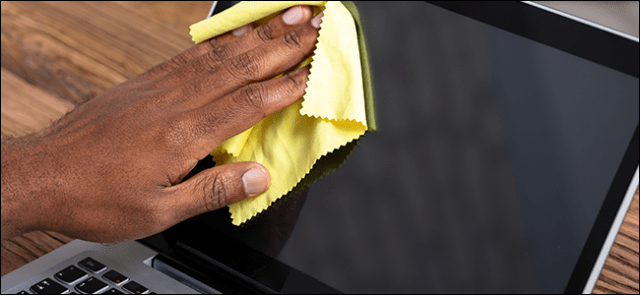 A human hand cleaning a laptop screen with a microfiber cloth.
