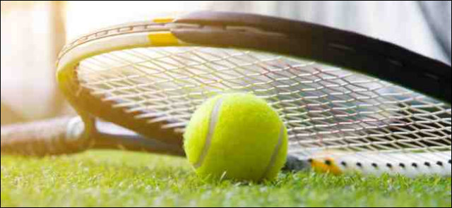 Tennis ball and racket on turf