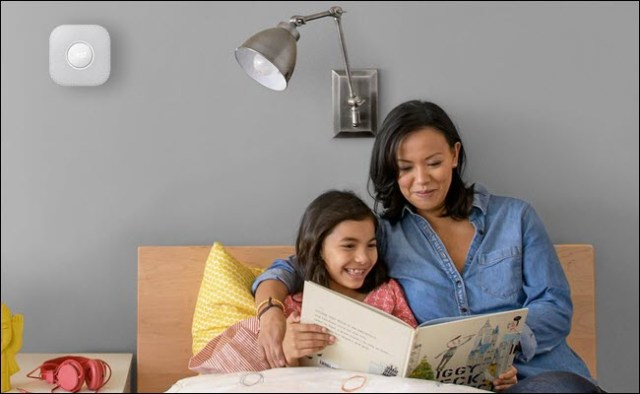 A mother and her child reading a children's book in bed, with a Nest Protect mounted on the wall above their head.