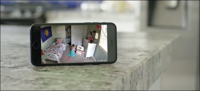 An iPhone showing a Wyze Cam thread of a child playing in his room.