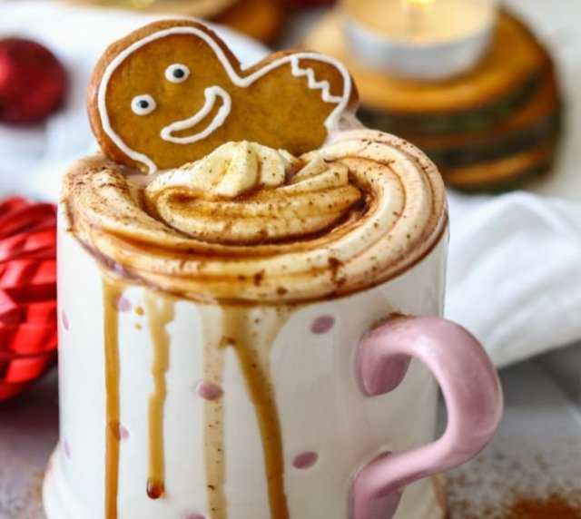A white and pink cup filled with hot coconut gingerbread, topped with whipped cream and a gingerbread man cookie. The sticky cup is full of hot chocolate and drips down the cup.
