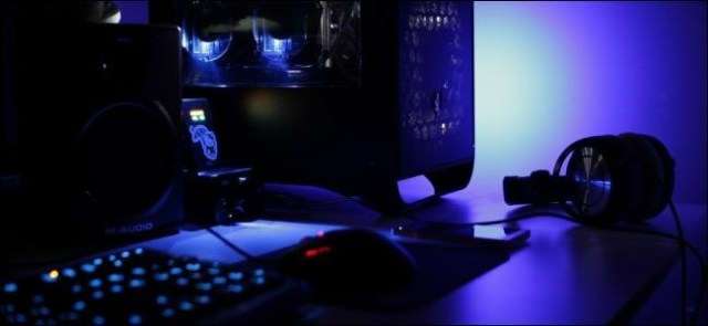 Desktop and headphones on a desk in a dimly lit room.