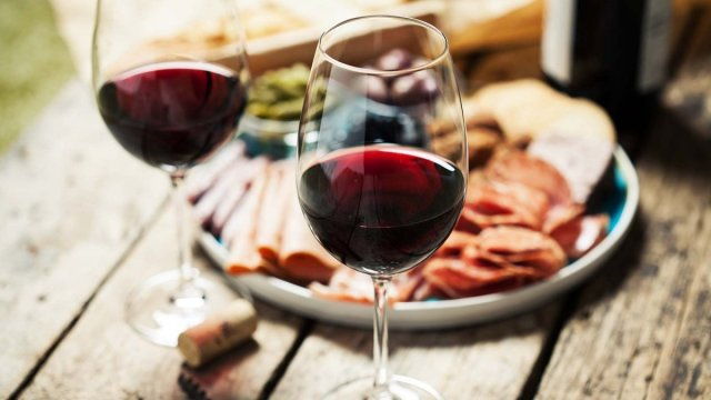 Two glasses of red wine on a rustic table in front of a platter of cold meats.