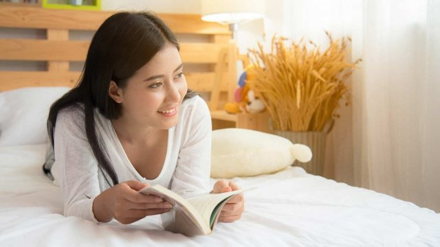 Woman reading a book, lying on her bed.