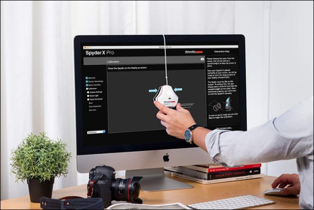 A Datacolor SpyderX Pro monitor calibration tool hanging from the front of a computer screen.