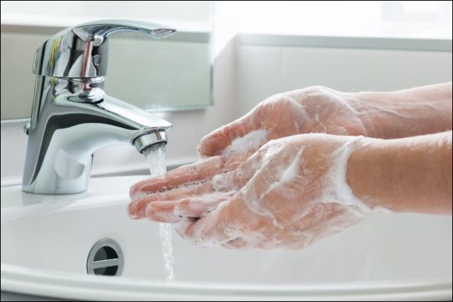 Wash hands with soap under a water tap.