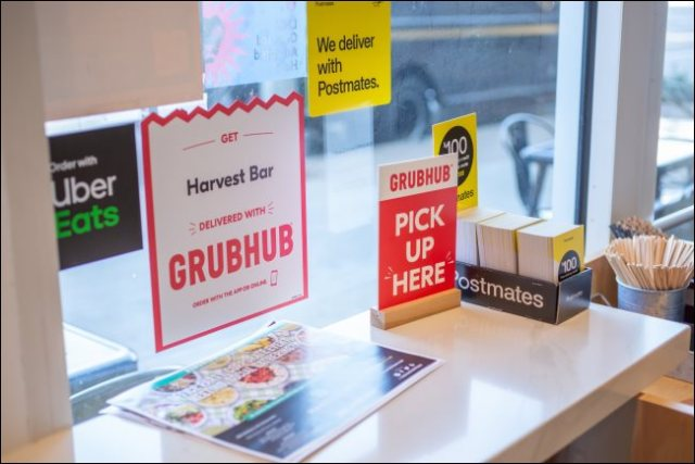 Signs for GrubHub, Postmates and Uber Eats in a restaurant.