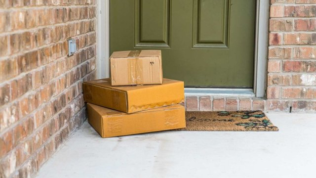A stack of parcels sitting on a porch in front of someone's front door on their welcome mat.