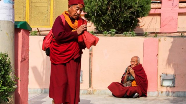 Two monks greet each other as they pass.