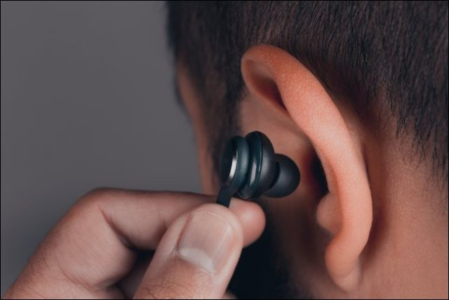 A man inserting a headset into his ear.