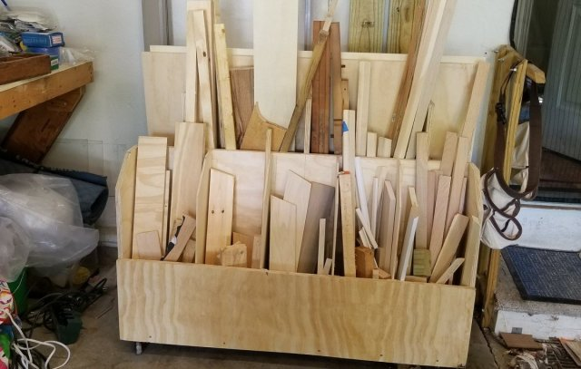 A set of wood neatly stacked in the individual slots of a cart.