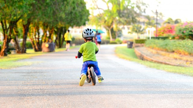 A child sliding on a balance bike.