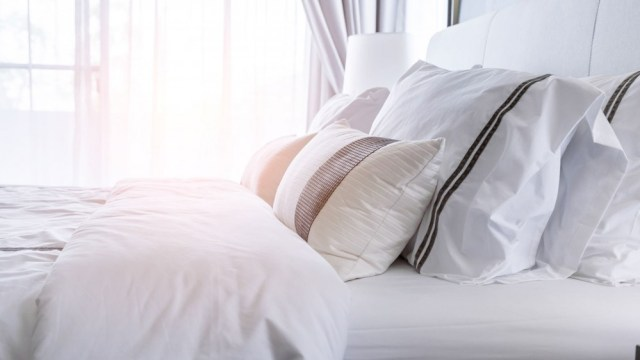 A bed fitted with high quality sheets and soft pillows.