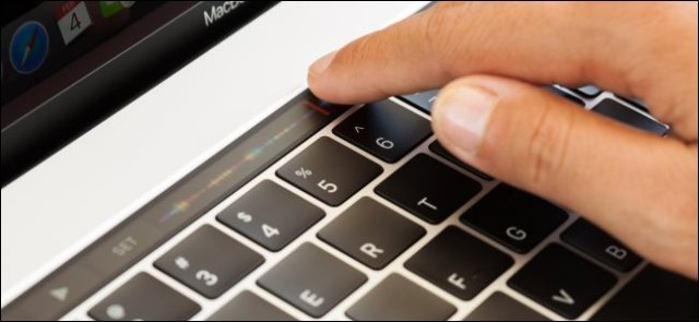 A hand touching the touch bar of a MacBook Pro.