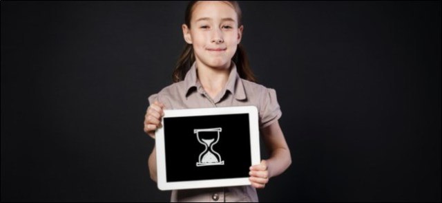 Girl holding a tablet with a digital drawing of an hourglass on it.