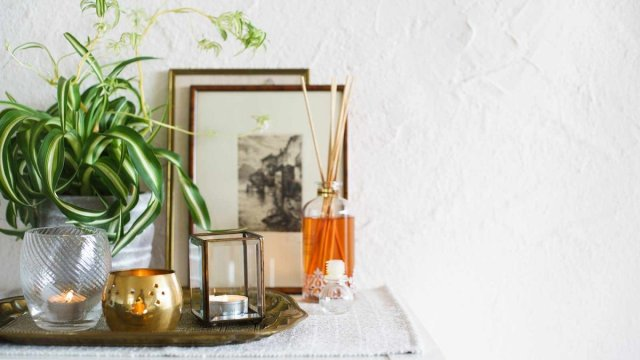 Candles and a scent diffuser on a small table in front of a plant and framed artwork.