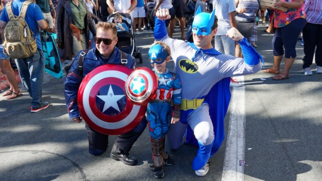 People wearing superhero costumes and taking photos outside of San Diego Comic-Con in 2019