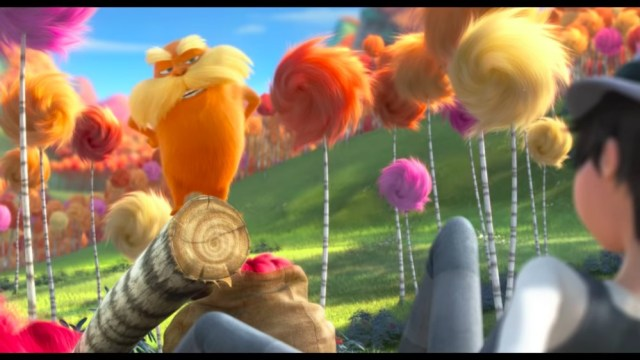 The character of Dr. Suess, the lorax, stands on top of a stump.