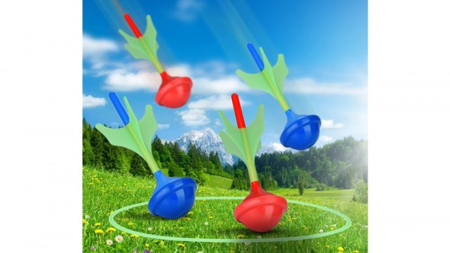 Lawn darts flying through the air towards glow in dark target rings