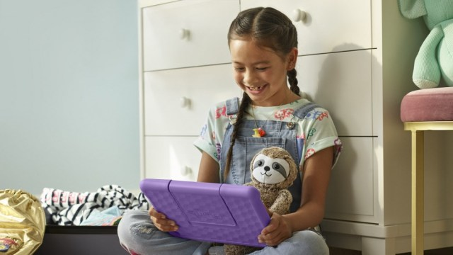 A young girl looking at an Amazon Kids + Fire tablet