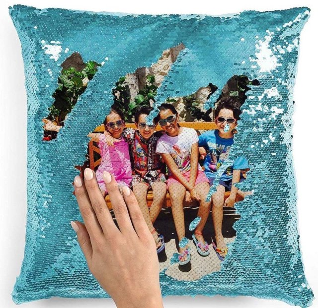 A turquoise sequined pillow with a picture of four children sitting on a bench.