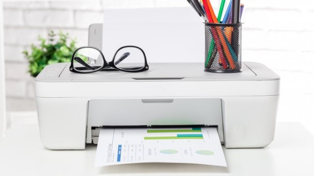 A printer on a desk with papers, glasses and writing utensils