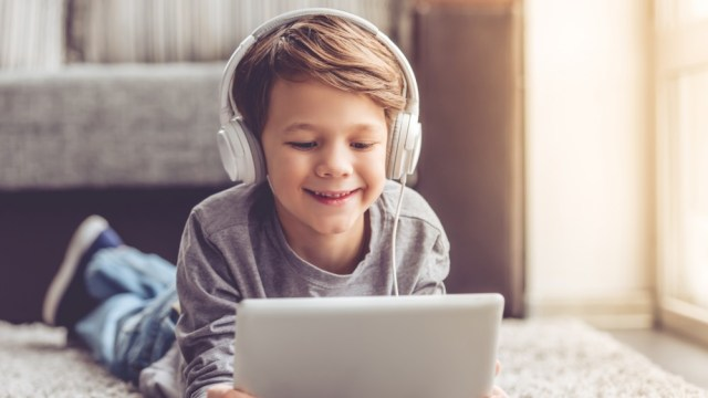 Small child wearing headphones while using a tablet
