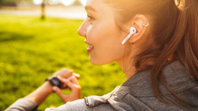 Sporty woman in her twenties in sportswear using smartwatch and wireless headphones while resting in a park