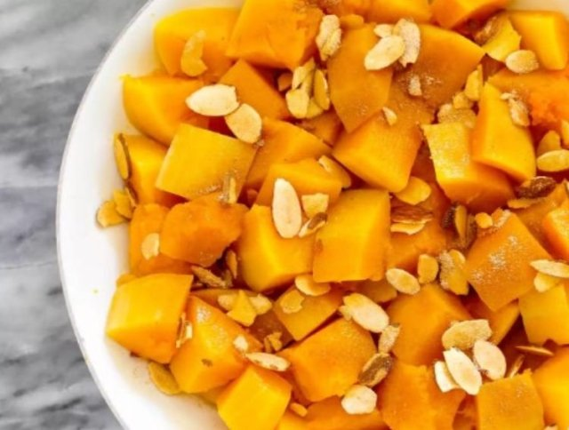 A plate of butternut squash, garnished with slivered almonds.