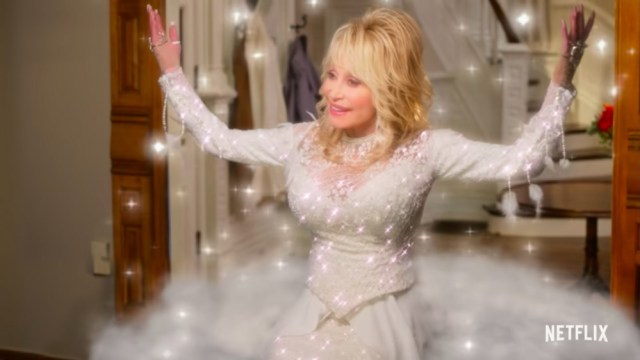 Dolly Parton stands in a hall in a white sequined dress.