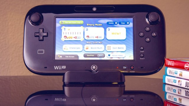 Wii U game console on a shiny table with Wii U games next to it
