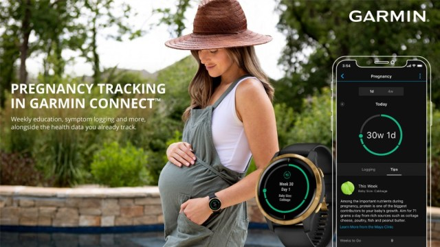 A woman is holding her pregnant belly while wearing, uh, a romper? Jumper? I do not know what it is. A Garmin watch and the Connect app are on the side showing the new pregnancy tracking features