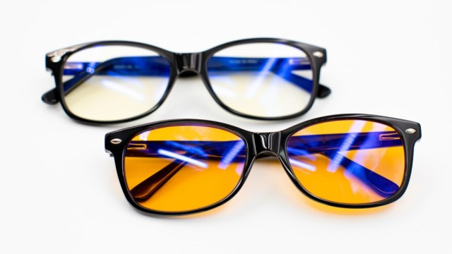Two pairs of blue light blocking glasses on a white background