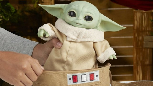 A baby Yoda Animatronic in a fabric carry bag.