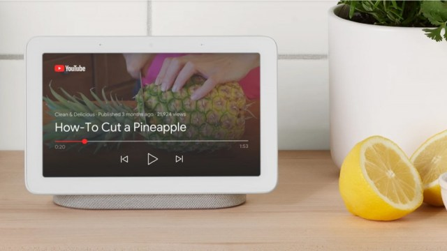 Google Nest Hub smart display with YouTube video playing set on kitchen countertop next to lemons