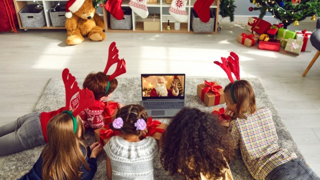 A group of children watching a video chat with Santa Claus using a laptop in a festively decorated house