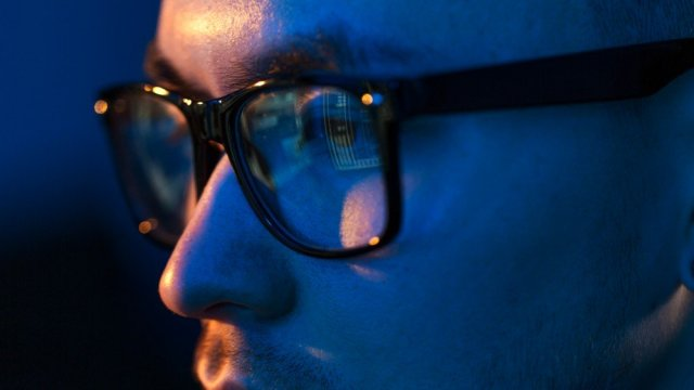 Close up of a person wearing glasses looking at a computer screen in the dark