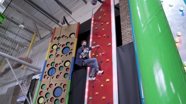 A man at the top of a climbing wall with a grappling hook on his arm.