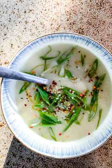 Delicious celery root soup in a bowl, garnished with green onions and chili flakes.