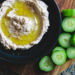 a plate of white bean hummus with sliced cucumbers on the side.