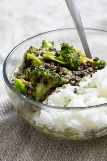 a bowl of black lentil and broccoli curry over steamed jasmine rice