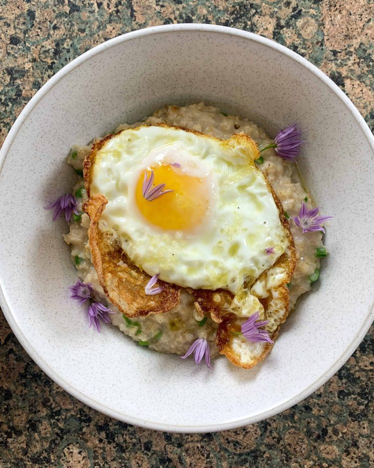 Bowl of savoury porridge with a fried egg and chive flowers