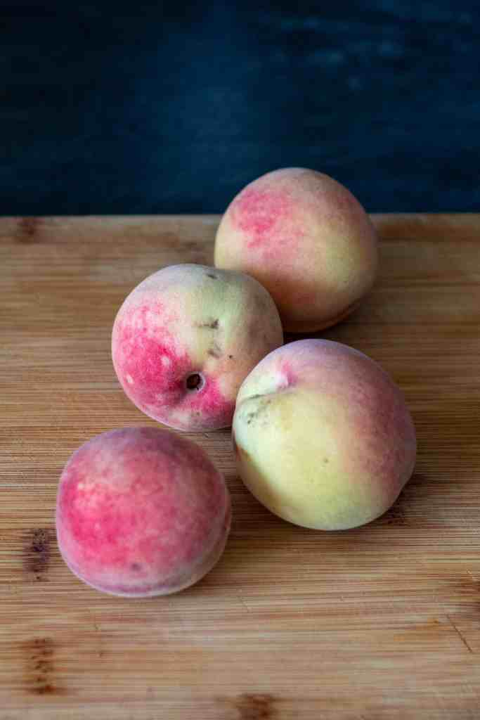 four peaches on a cutting board.