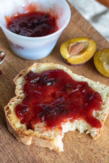 plum and ginger jam on toast with a cut fresh plum next to it.